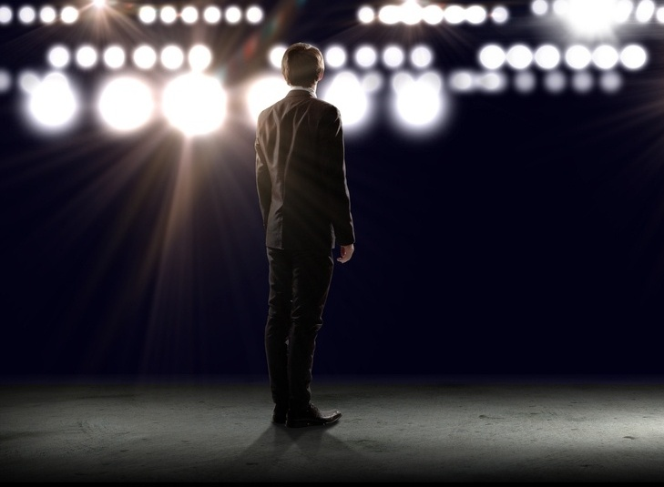 businessman standing in lights of stage